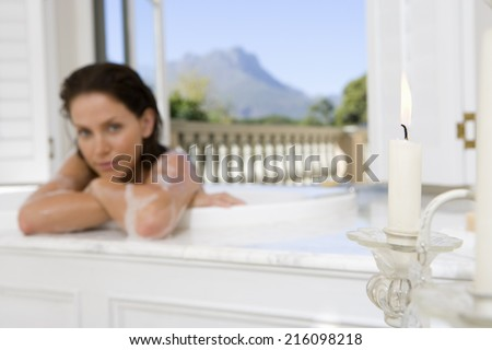 Young woman in bath, portrait, focus on candle in foreground - stock photo