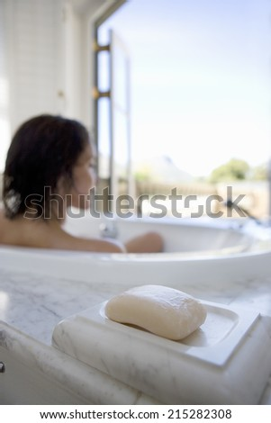 Young woman in bath, rear view, soap in foreground