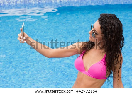 Young woman in bathing suit taking selfie