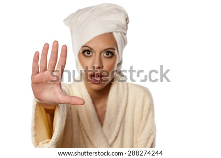 young woman in bathrobe and towel on her head showing a stop sign with her hand