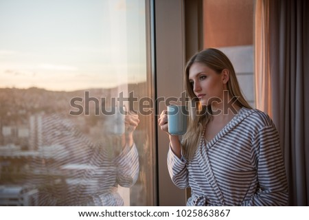 young woman in bathrobe enjoying evening coffee and beautiful sunset landscape of the city while standing by the window