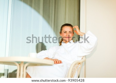 Young woman in bathrobe sitting at table on terrace and thinking