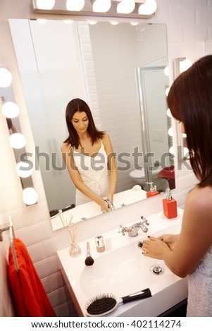 Young woman in bathroom washing hands, getting ready.