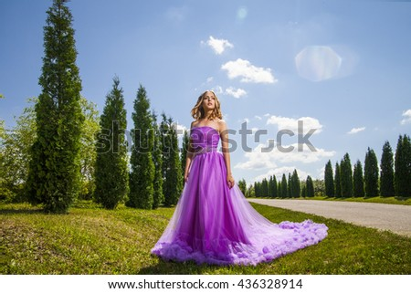 Young woman in beautiful dress amongst trees