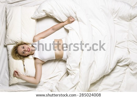 Young woman in bed - stock photo