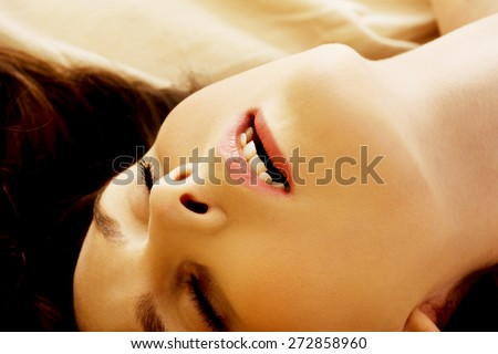 Young woman in bed getting orgasm. - stock photo