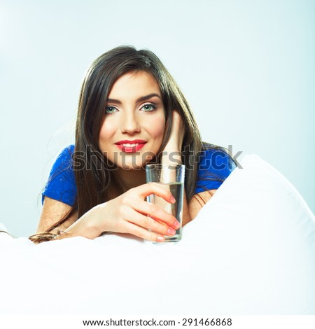 Young Woman in bed holding water glass. Smiling model. - stock photo