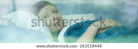 Young woman in bed suffering from cancer - stock photo