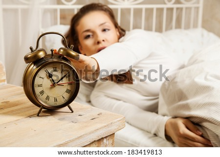 Young woman in bed turning off alarm clock