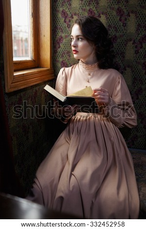 Young woman in beige vintage dress of early 20th century reading book in coupe of retro railway train - stock photo