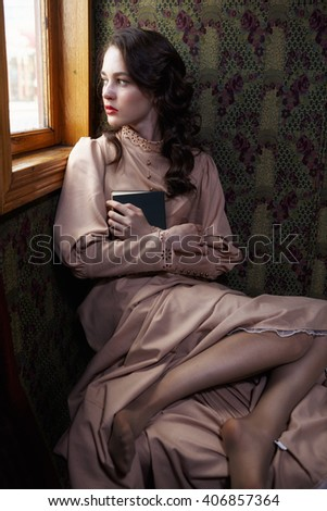 Young woman in beige vintage dress of early 20th century sitting near window in coupe of retro railway train - stock photo
