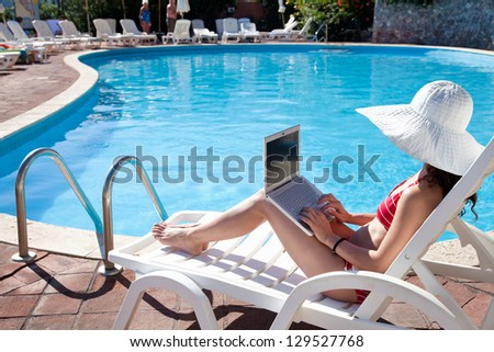 Young woman in big hat relaxing near the pool with laptop - stock photo