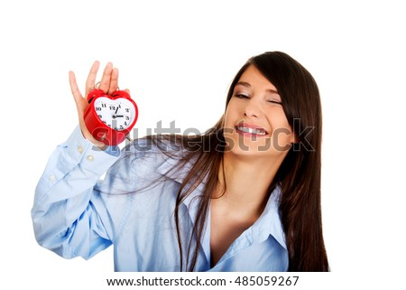 Young woman in big shirt holding alarm clock.