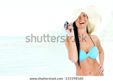 Young woman in bikini and straw hat on a seashore background - stock photo