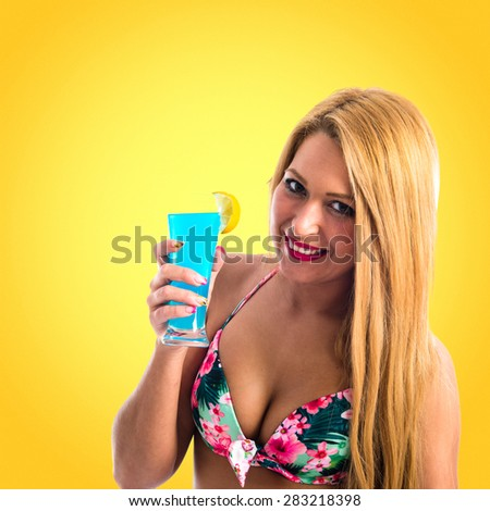 Young woman in bikini drinking a cocktail over colorful background