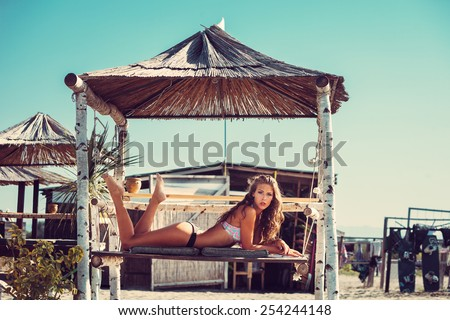 young woman in bikini  lie at shade at seaside beach enjoy in summer hot sunny day, full body shot - stock photo