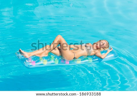 Young woman in bikini on a lilo in the swimming pool - stock photo