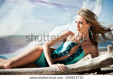 Young woman in bikini posing near a snag on a beach - stock photo