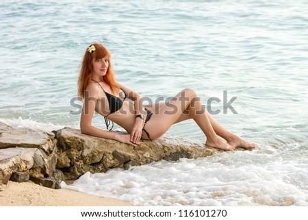 Young woman in bikini posing on sea coast sitting