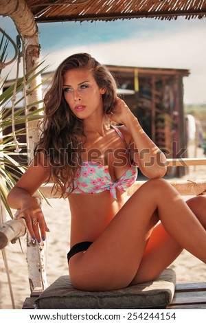 young woman in bikini  sit at shade at seaside beach enjoy in summer hot sunny day - stock photo