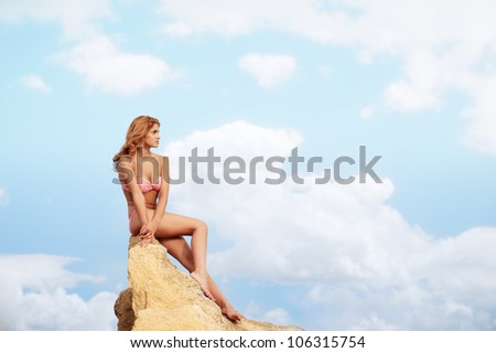 Young woman in bikini sitting on the yellow rock with cloudy sky on background - stock photo