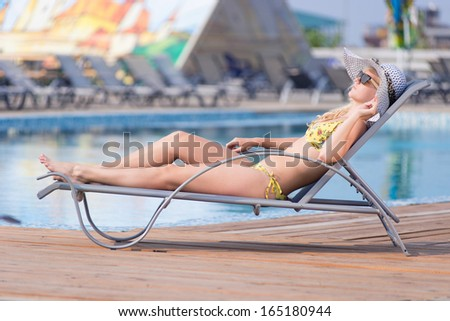 Young woman in bikini, sunglasses,  hat and swimsuit laying on chaise-longue and sunbathing by the pool in a summer vacation  - stock photo