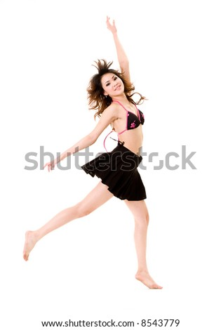 young woman in bikini top & skirt jumping freely and happily