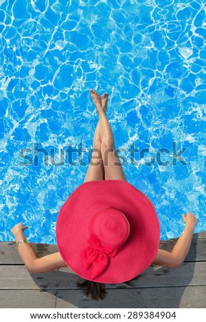 Young woman in bikini wearing a red straw hat sitting in the swimming pool - stock photo