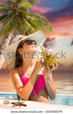 Young woman in bikini wearing a straw hat and drinking a fresh cocktail in the swimming pool at sunset - stock photo