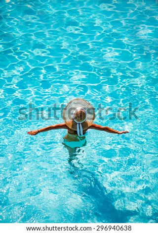 Young woman in bikini wearing a straw hat at the swimming pool - stock photo