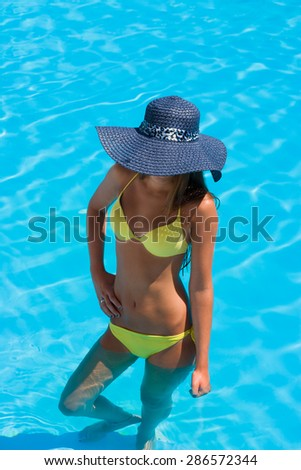 Young woman in bikini wearing a straw hat by the swimming pool - stock photo