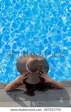 Young woman in bikini wearing a straw hat sitting in the swimming pool - stock photo