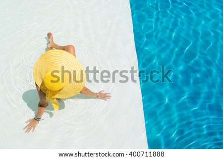 Young woman in bikini wearing a yellow straw hat by the swimming pool