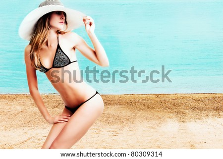 young woman in bikini wearing hat on the beach - stock photo