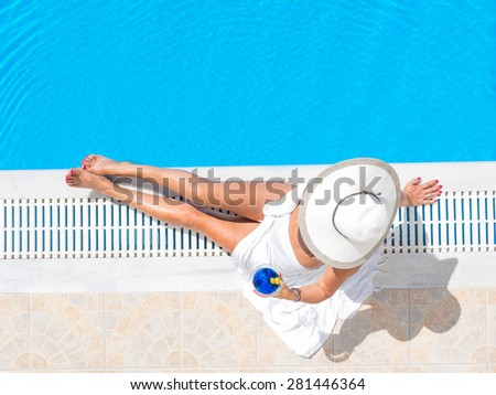 Young woman in bikini with a straw hat by the swimming pool - stock photo
