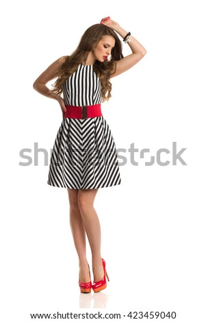 Young woman in black and white striped dress and high heels posing with hand on head and looking away. Full length studio shot isolated on white. - stock photo