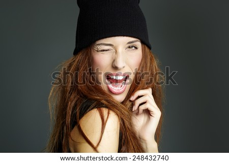 Young woman in black beanie winking and smiling. - stock photo