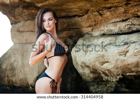 Young woman in black bikini posing on a sand rocks near the sea - stock photo