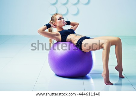 Young woman in black clothing with fitness ball in modern white interior. Tattoo on body.