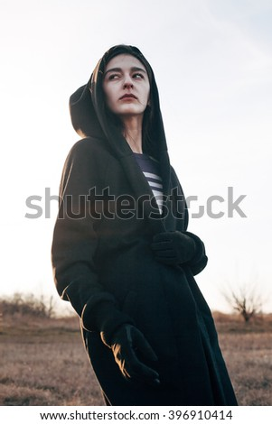 Young woman in black coat walking outdoors.