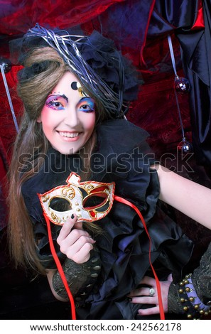 Young woman in black dress and with artistic make-up posing with mask - stock photo