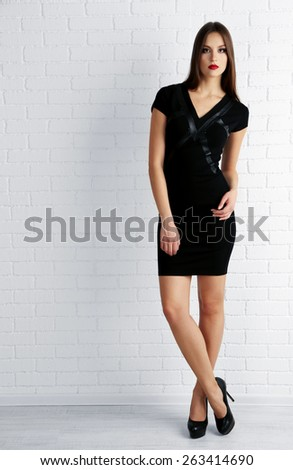 Young woman in black dress on white brick wall background - stock photo