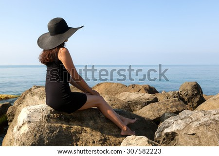 Young woman in black hat on the sea rocks