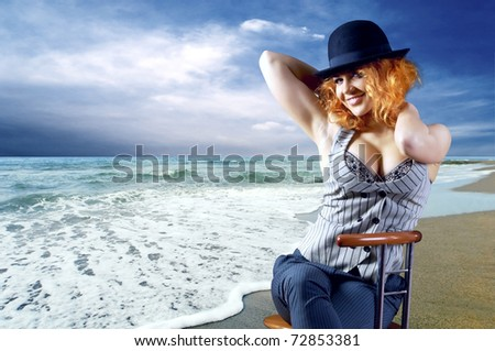 Young woman in black hat seating on the beach