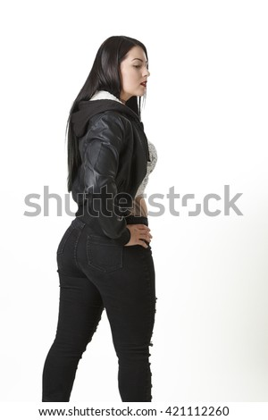 young woman in black jean and coat turning around