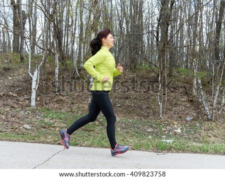Young woman in black leggings running in nature.  Fitness, sports. Lifestyle.   - stock photo