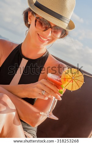 Young woman in black swimsuit with cocktail on the beach in tropics - stock photo