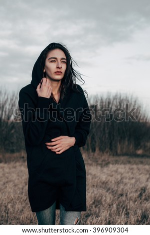 Young woman in black walking across the field. depressive mood state