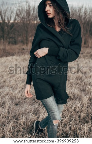 Young woman in black walking outdoors. depressed mood