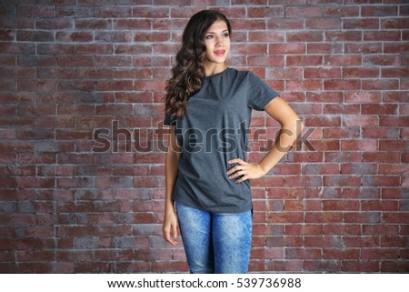 Young woman in blank grey t-shirt standing against brick wall